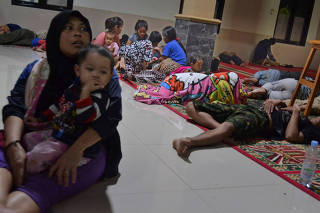 Residents sit inside a mosque as they evacuated following high waves and the eruption of Anak Krakatau volcano at Labuan district in Pandeglang regency