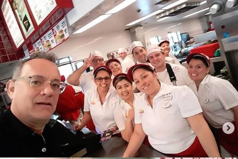 O ator Tom Hanks tira selfie com funcionários e visitantes de uma rede de lanches