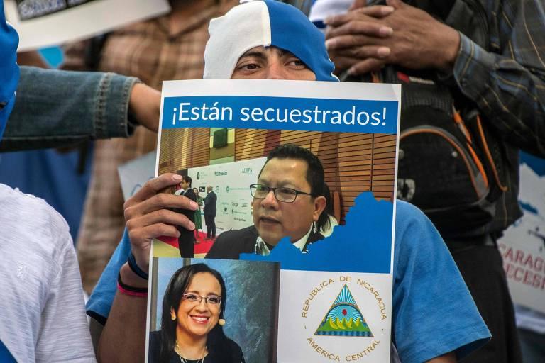 Nicaraguense segura fotos dos jornalistas Miguel Mora e Lucía Pineda, pedindo sua libertação