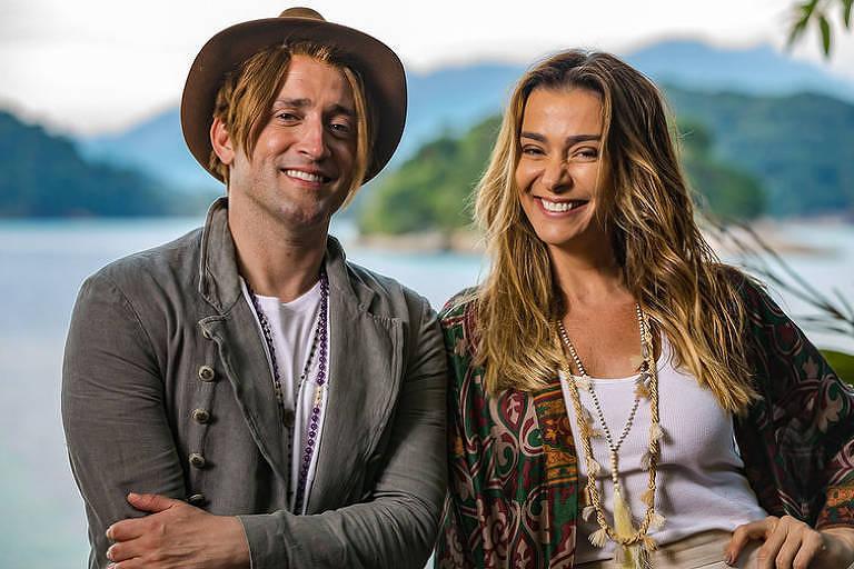 Os atores Paulo Gustavo e Mônica Martelli sorriem para foto, com o mar ao fundo