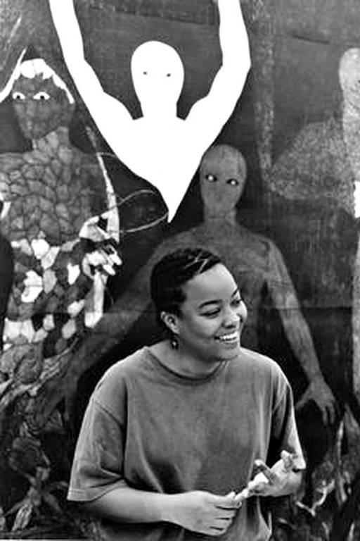 artista posa em frente à obra de arte