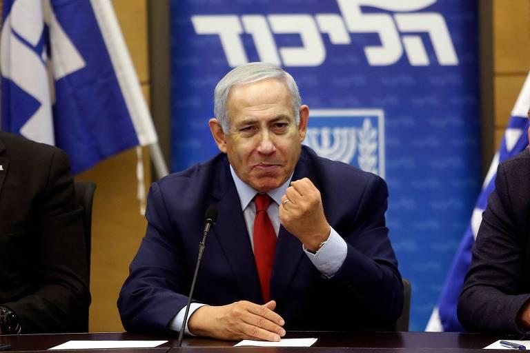 Netanyahu, sentado diante de uma escrivaninha, faz sinal de vitória com pulso cerrado
