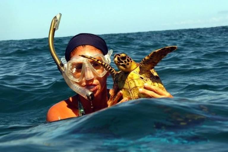 Mulher no mar segura tartaruga