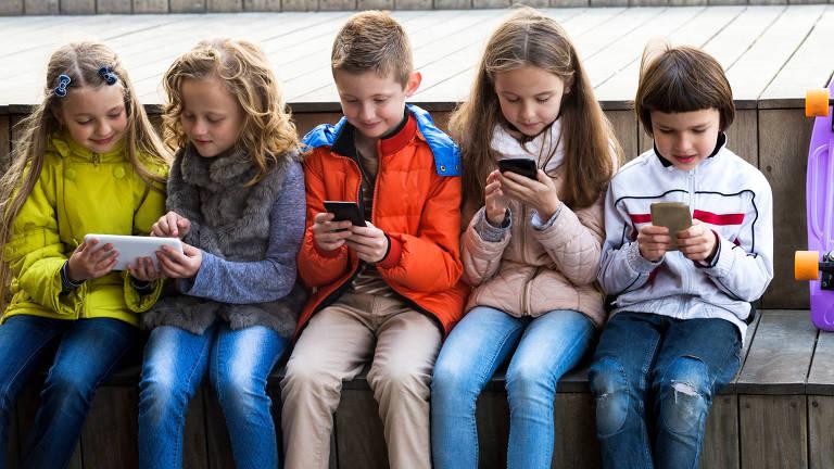 Meninos e meninas brincam com celulares, sentados uns ao lado dos outros