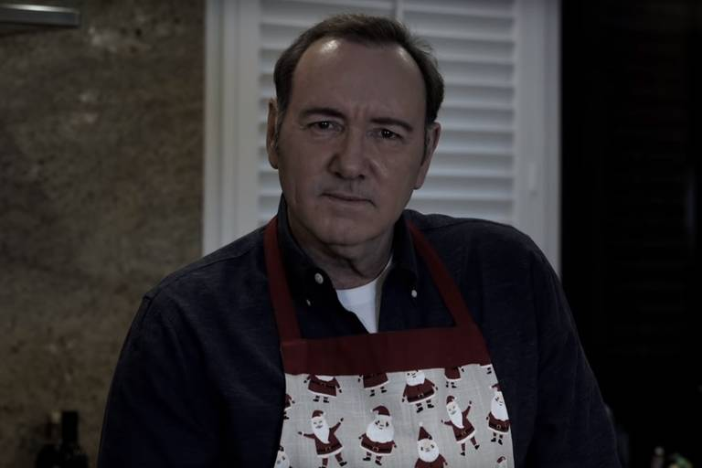 Kevin Spacey olha para a câmera e veste avental com estampa de Papai Noel