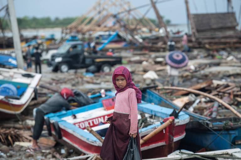 Menina caminha entre escombros após tsunami na província de Pandeglang, na Indonésia