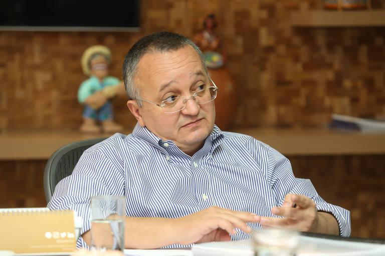 O governador de Mato Grosso, Pedro Taques, em entrevista à Folha, sentado diante de uma mesa. Ele usa óculos e camisa com listras verticais finas