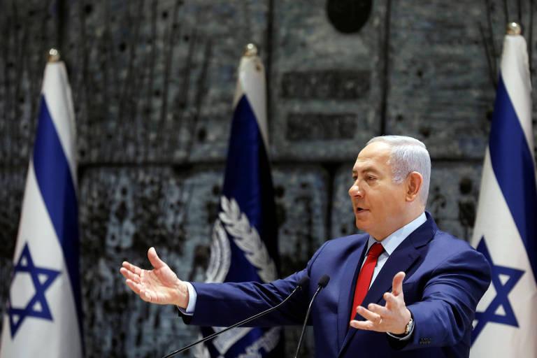 De braços abertos e diante de duas bandeiras de Israel e de uma terceira não identificada, Netanyahu discursa em um púlpito