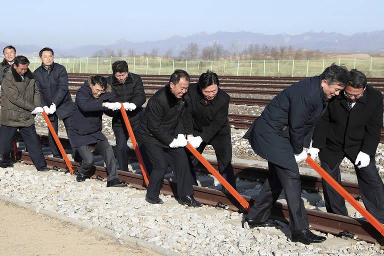Funcionários dos governos da Coreia do Sul e da Coreia do Norte conectam trilhos de ferrovia em cerimônia em Kaesong, Coreia do Norte