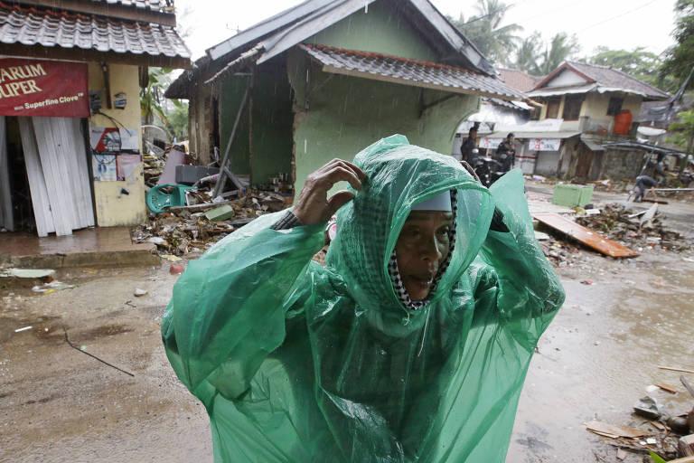 Homem com capa de chuva em meio a destroços em Carita, na Indonésia, nesta quarta (26)
