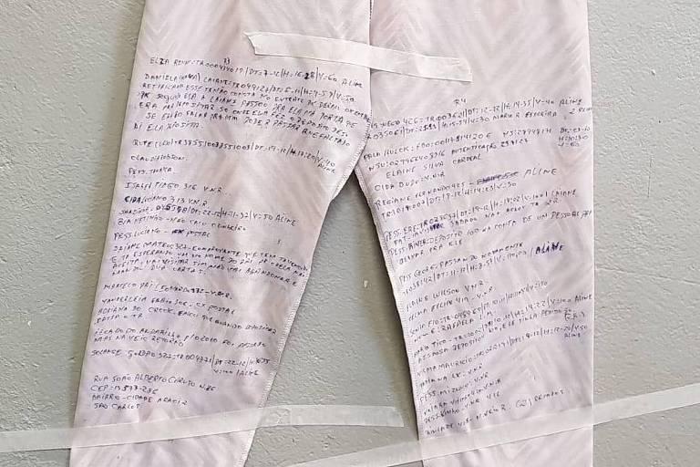 calça branca com várias palavras escritas em caneta azul