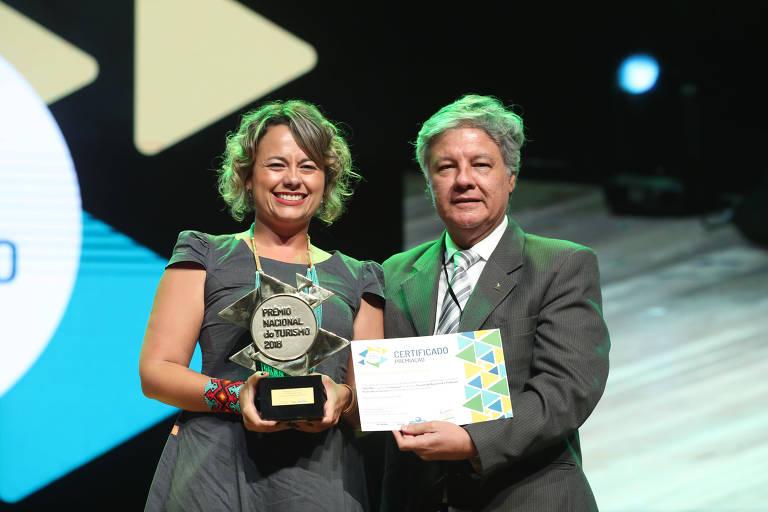 Marianne Costa, fundadora da Vivejar e integrante da Rede Folha de Empreendedores Socioambientais, recebe de Bob Santos, secretária do Ministério do Turismo, o Troféu Ouro do Prêmio Nacional do Turismo na categoria Turismo de Base Local e Produção Associada ao Turismo