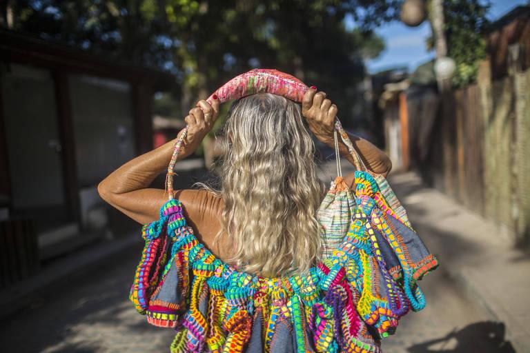 e2d73f4e0bba Mulher loira, de costas, segura um arco com calcinhas de biquíni  penduradas. Peças