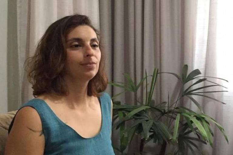 A professora Priscila Luana Pereira, 33, mãe do filho brasileiro de Cesare Battisti. Ela mora com o menino, de cinco anos, em São José do Rio Preto (SP). Está sentada em um sofá com blusa regata azul e calça jeans. Está de pernas cruzadas.