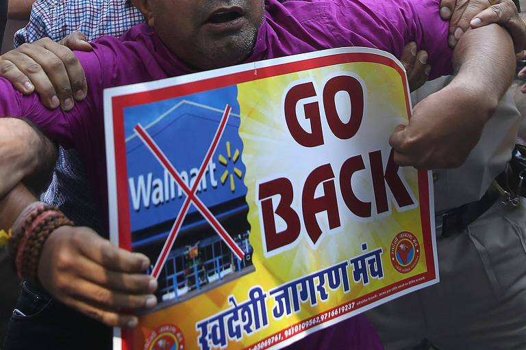 Manifestante indiano exibe cartaz contra o Walmart, na época de seu acordo com a gigante de vendas online indiana Flipkart, em Nova Déli; o Ministério do Comércio da Índia anunciou que vai apertar as regras de comércio eletrônico