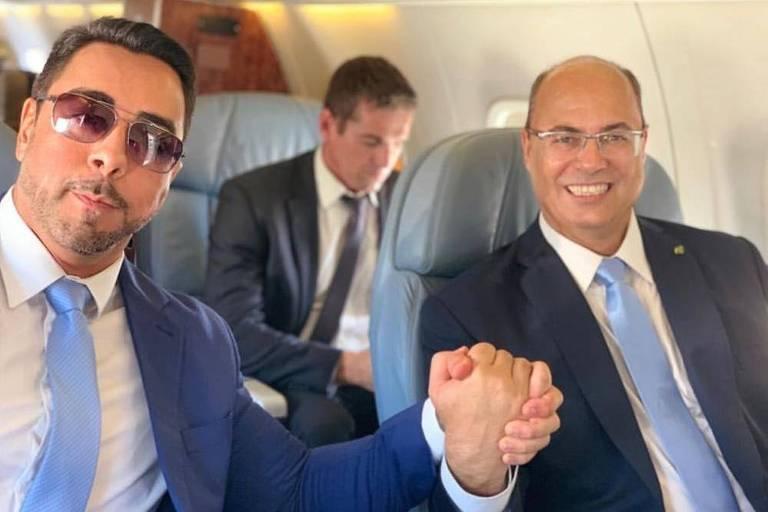 O juiz Marcelo Bretas segura a mão do governador do Rio, Wilson Witzel, durante carona em voo da FAB para Brasília