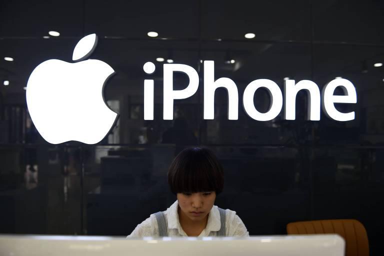 Vendedora em loja da Apple em Pequim; gigante de tecnologia pode sofrer com guerra comercial entre Estados Unidos e China Shop