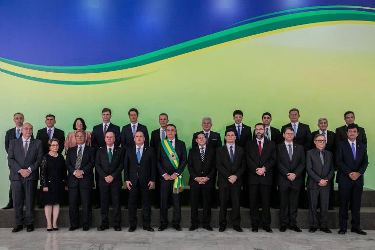 Em frente a uma parede amarela, verde e azul, o presidente Bolsonaro posa com seus ministros no dia da posse. Estão posicionados em duas fileiras e vestidos na cor preta, com exceção da ministra Damares Alves, que usa um vestido rosa. Os homens, que são o restante dos fotografados com exceção de uma senhora, estão de terno e com as mãos cruzadas em frente ao corpo.