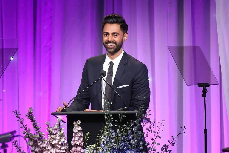 Em um fundo púrpura, o comediante Hasan Minhaj, usando terno e gravata, discursa em um palanque com microfone