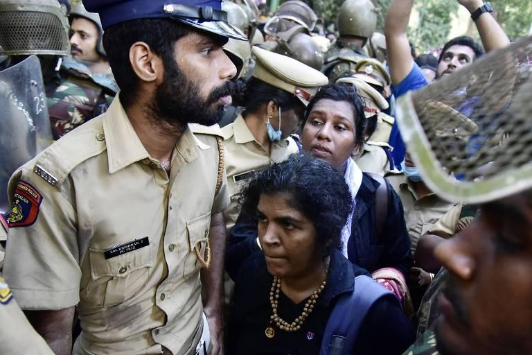 Duas mulheres Kanaka Durga (ao centro) e Bindu (atrás) são escoltadas por policiais depois de tentarem entrar no templo pela primeira vez em dezembro