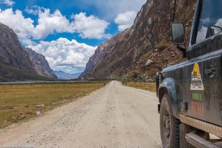 Carro anda em estrada de terra em vale com montanhas nas laterais