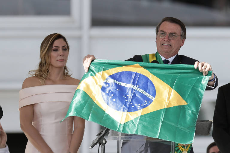 O presidente Jair Bolsonaro abre a bandeira do Brasil após discurso no parlatório ao lado da primeira-dama, Michelle