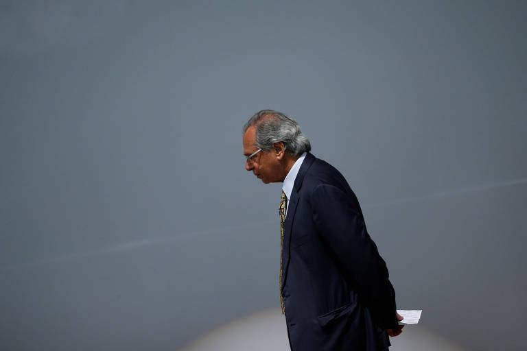 Retrato de Paulo Guedes caminhando com as mãos cruzadas nas costas