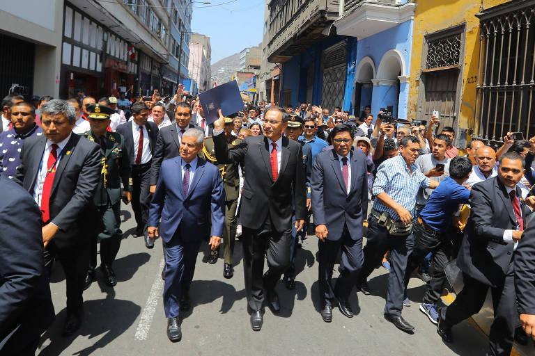 Acompanhado por manifestantes e integrantes do governo, o presidente Martin Vizcarra (centro, de gravata vermelha) chega ao Congresso para apresentar o projeto de lei que permite uma intervenção no Ministério Público