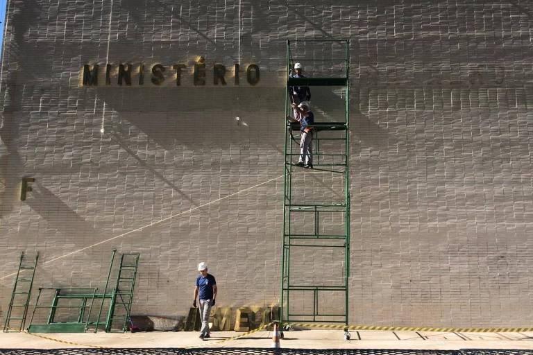 Homens retiram letreiro do prédio onde funcionava o Ministério do Trabalho