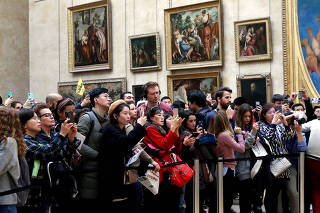 FILE PHOTO: Visitors take pictures of the painting