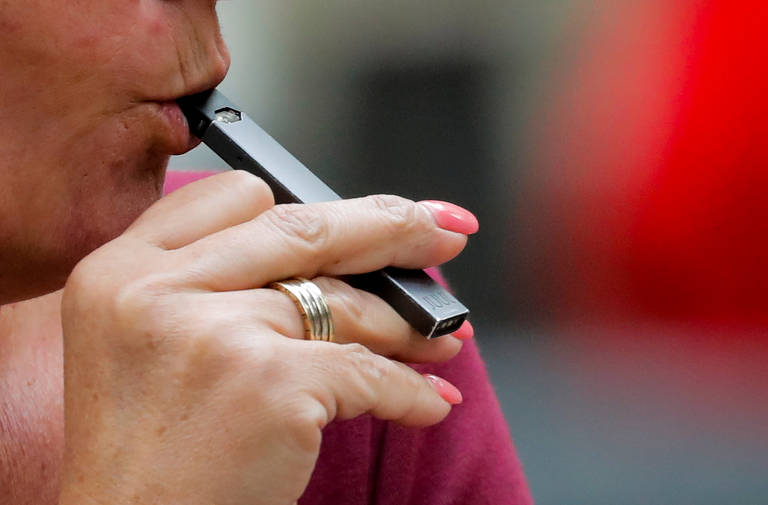 FILE PHOTO: A woman smokes a Juul e-cigarette in New York