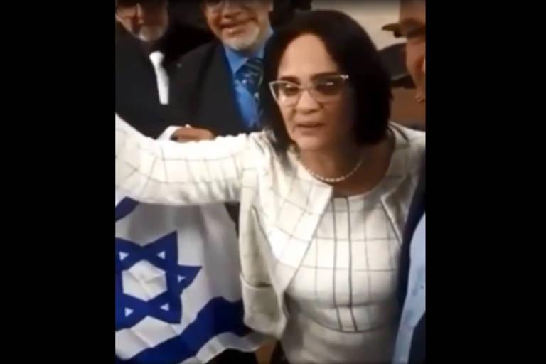 """Frame de vídeo mostra a pastora evangélica Damares Alves, ministra da Mulher, Família e Direitos Humanos, dizendo que é uma """"nova era no Brasil"""" que """"menino veste azul e menina veste rosa"""", com a bandeira de Israel ao fundo."""