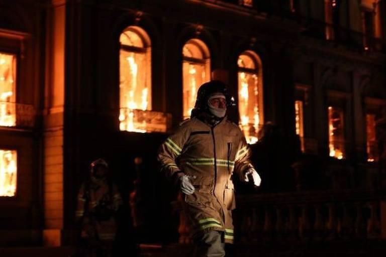 Bombeiro sai de prédio em chamas