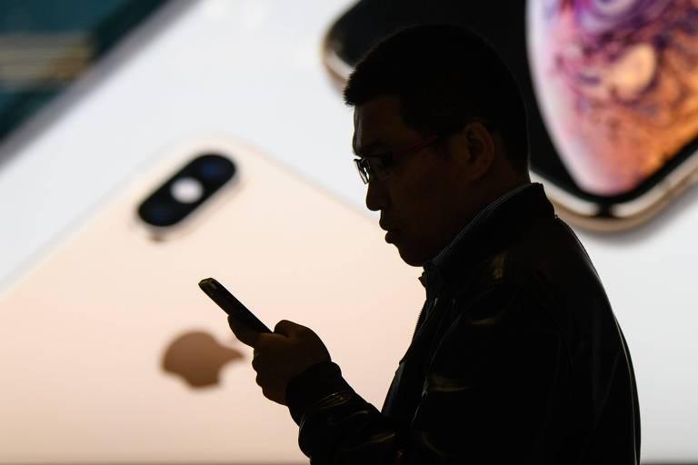 Homem usa smartphone em frente à loja da Apple em Hong Kong; consumo mais frio na China impactou na previsão de receita da gigante americana