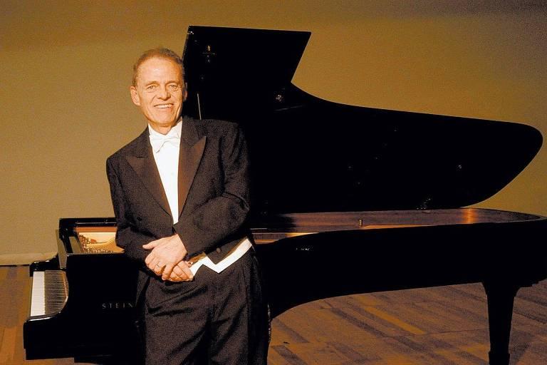 homem sorri encostado a um piano