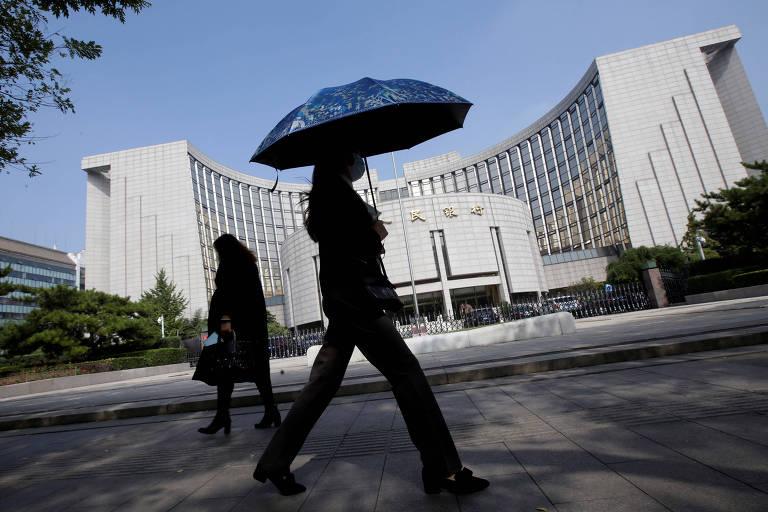 Pessoas caminham em frente ao Banco Popular da China, em Pequim