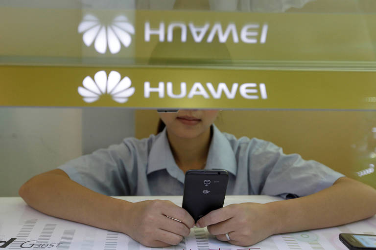 Mão de vendedora da Huawei segurando smartphone