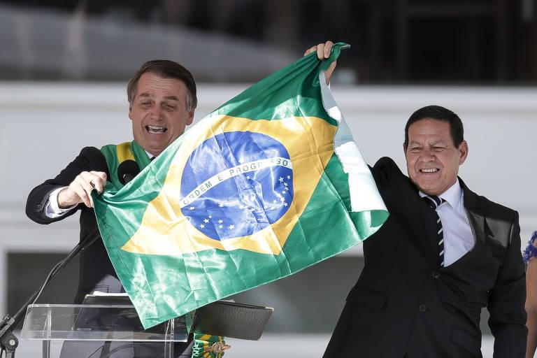 O presidente Jair Bolsonaro, ao lado do vice, general Hamilton Mourão, com a bandeira do Brasil na cerimônia de posse, no começo de 2019, no Palácio do Planalto, em Brasília