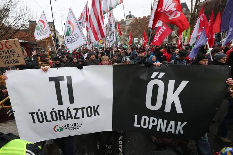 """Manifestantes protestam em Budapeste contra nova lei trabalhista, levando cartazes com os dizeres """"Você faz hora extra, eles roubam"""""""