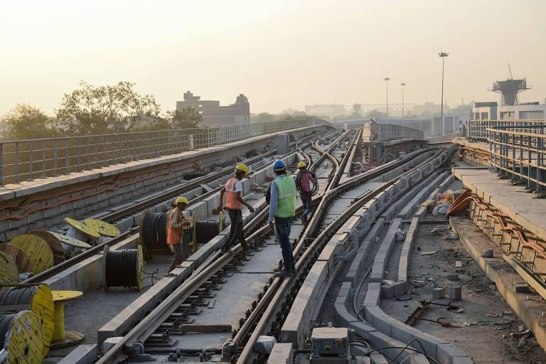Indianos trabalham em linha ferroviária em Ahmedabad, na Índia