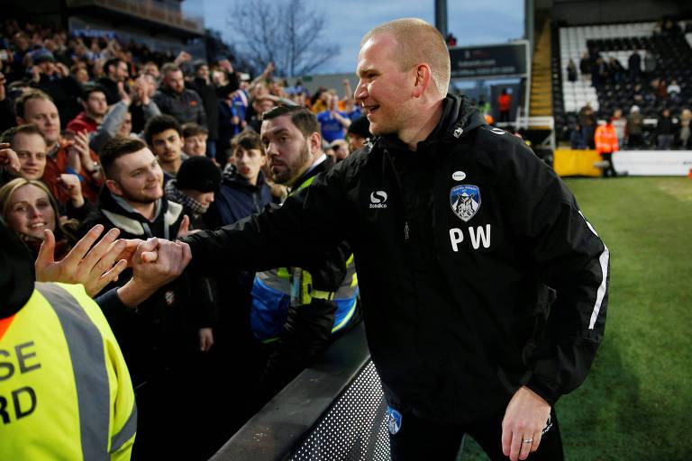 Pete Wild, técnico interino do Oldham Athletic, cumprimenta torcedores após classificação na Copa da Inglaterra