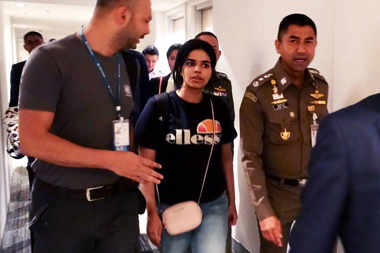 Rahaf al-Qanun (no centro) é escoltada por oficiais da imigração tailandesa e do Acnur no aeroporto de Bancoc