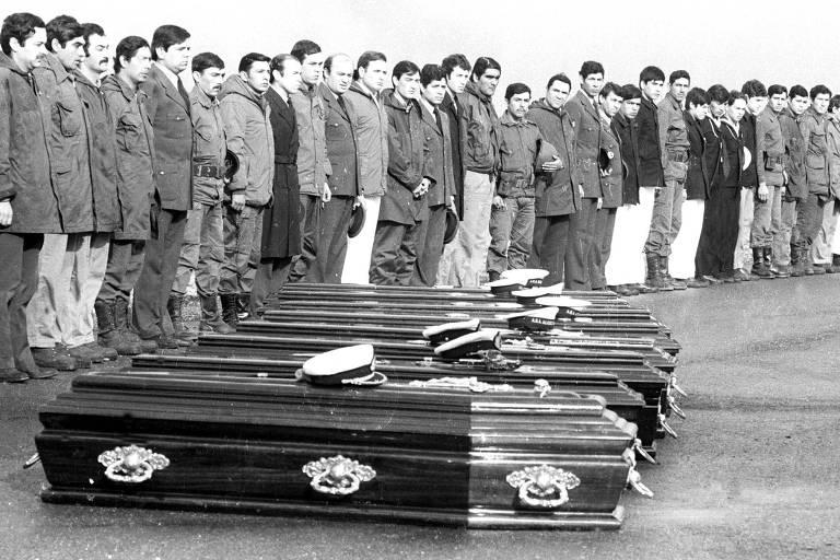 Em foto preto e branca, vários homens lado a lado olham para caixões no chão