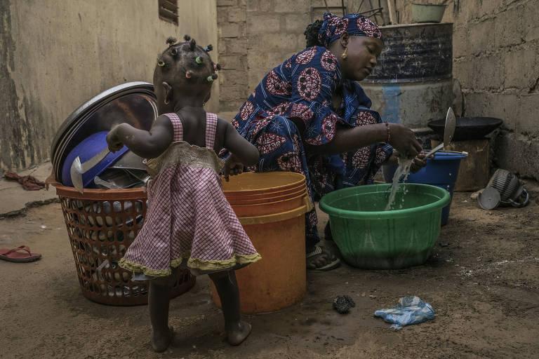 Hajara, que se divorciou do marido e voltou a morar com a família, lava louça perto da filha em Maradi