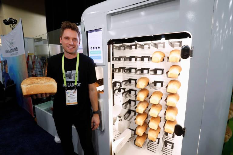 Homem segura pão ao lado de máquina que faz o alimento