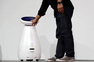 Yoon Lee, a Samsung America senior vice president, has his vital signs taken by Samsung Bot Care, a healthcare robot, during a Samsung news conference at the 2019 CES in Las Vegas