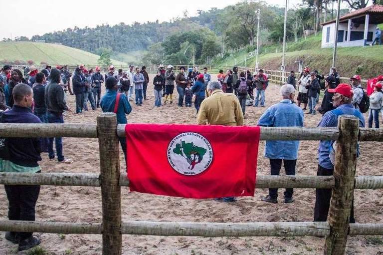 Pessoas no meio de uma cerca, com uma bandeira do MST