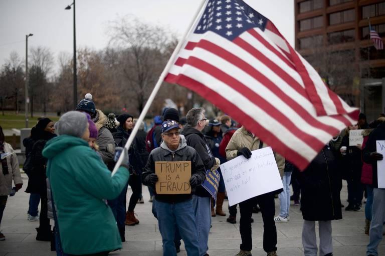 manifestantes seguram cartazes e uma bandeira dos estados unidos ao ar livre