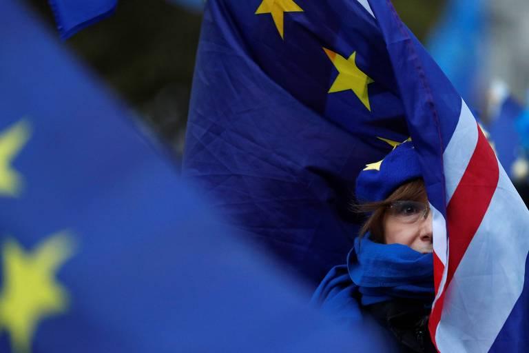 Manifestante contrária ao 'brexit' com bandeiras do Reino Unido e da União Europeia durante protesto do lado do Parlamento em Londres