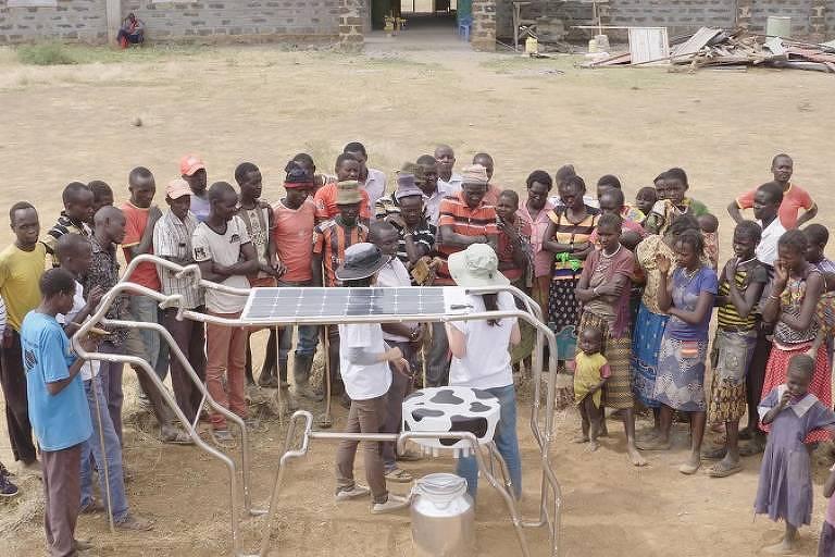 Crianças e adultos ao redor do aparalho, que é uma placa solar, com baterias brancas embaixo. A estrutura que segura a placa solar tem o formato do contorno de uma vaca